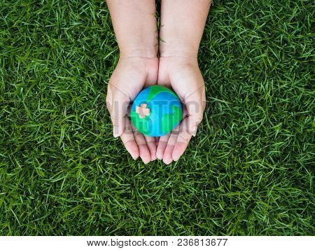 Earth Day. Earth In Hands And Green Grass Field Background. Environment Save Earth Concept.