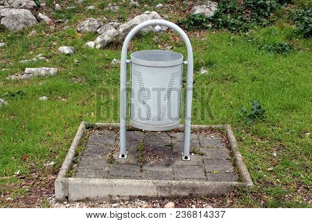 Grey Metal Trash Can Mounted On Stone Tiles And Surrounded With Uncut Green Grass, Fallen Leaves And