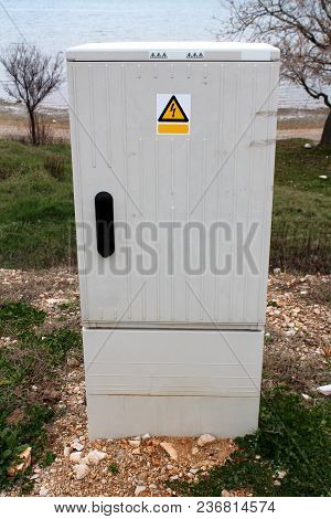 Outdoor Grey Electrical High Voltage Box Surrounded With Sand And Uncut Grass With Trees, Beach And