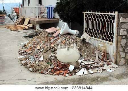 Pile Of Construction Material Waste In Courtyard, From Rubble, Sand, Broken Tiles, Toilet, Sink, Bri