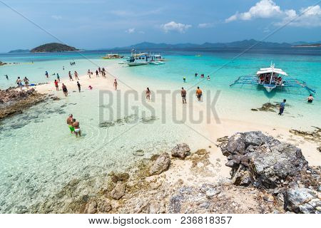 Coron, Philippines - March 28, 2018:  Tropical beach with tourists and boats on the Bulog Dos island, Palawan, Philippines