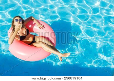 Sexy Girl Having Fun And Laughing On An Inflatable Pink Ring. Woman In Swimming Pool.