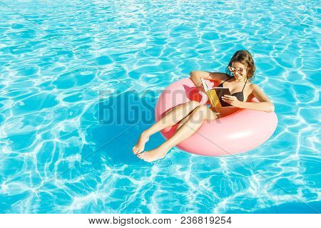 Beautiful Happy Woman Reading A Book With Inflatable Ring Relaxing In Blue Swimming Pool.