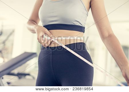Woman Check To Her Body At Gym. Sport And Reaction Concept. Vintage Tone.