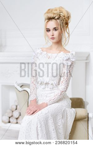 Portrait of a beautiful bride woman in elegant white wedding dress. Luxurious apartments.