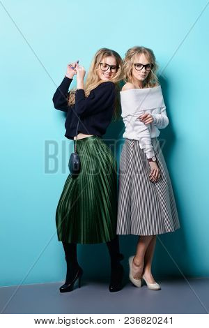 Two cheerful young women dressed in sweaters and skirts posing in the studio over blue background. Full length portrait. Winter fashion.