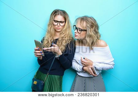Two pretty girls using their smartphones and  posing in studio over blue background. Modern lifestyle. Studio shot.