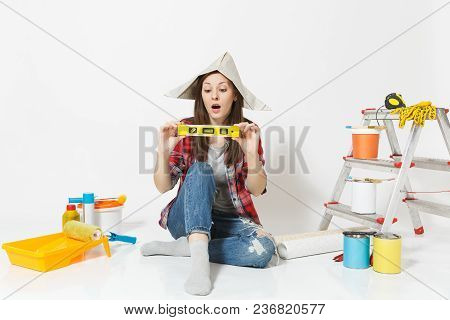Woman In Newspaper Hat Sitting On Floor With Building Bubble Spirit Level, Instruments For Renovatio