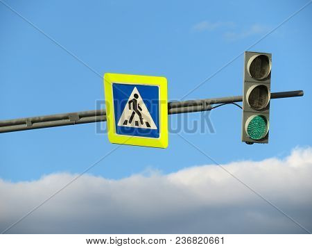 Pedestrian Crossing Sign And Green Traffic Light On Blue Cloudy Sky Background. Free Way Or Good Way