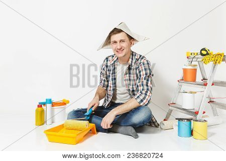 Man In Newspaper Hat Sitting On Floor, Using Paint Roller, Instruments For Renovation Apartment Room