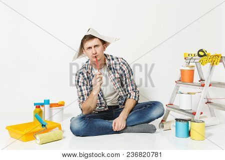 Pensive Man In Newspaper Hat With Pencil In Mouth, Sitting On Floor With Instruments For Renovation