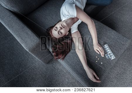 Medical Condition. Top View Of Despondent Beautiful Dolorous Woman Posing On Sofa While Counting Ant