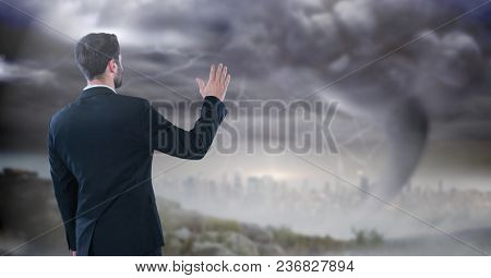 businessman with hand up in storm cityscape