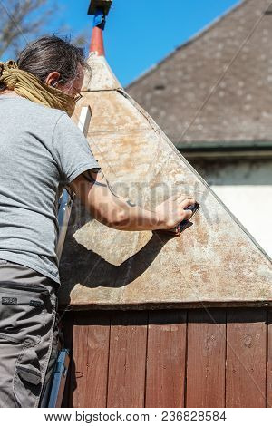 Man Sanding The Tin Roof Of His Backyard Shed With A Sanding Block, Removing Rust And Dirt