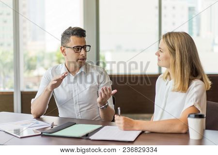 Serious Ceo Consulting Female Employee At Meeting. Young Caucasian Businessman Wearing Glasses Sitti