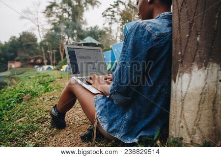 Woman alone in nature using a laptop on a camp site getaway from work or internet addiction concept