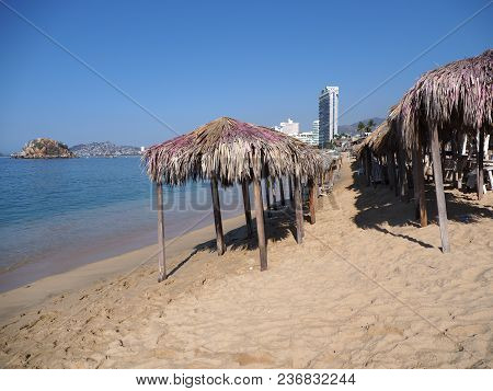 Exotic Bamboo Huts On Sandy Beach At Bay Of Acapulco City In Mexico With Skycraper And Waves Of Paci