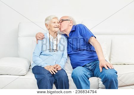 Happy senior hugs and kisses his wife on the sofa at home