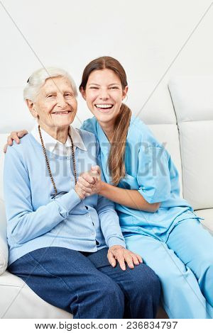 Smiling nurse on home care makes home visit to happy senior citizen