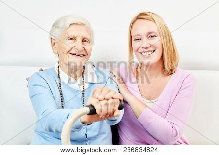 Happy senior mother as a mother and caring daughter at home on the sofa