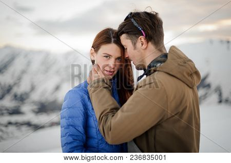 Slender Blue-eyed Girl Brunette Looking Into The Frame While Her Hugging Guy In A Brown Jacket Again