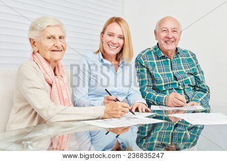 Family with young woman and senior couple solve puzzles as memory training