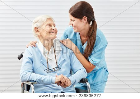 Female caregiver or nurse with an old woman in wheelchair
