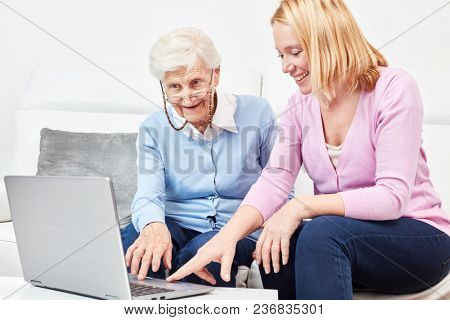 Young woman shows senior woman at the laptop computer the internet in a computer course