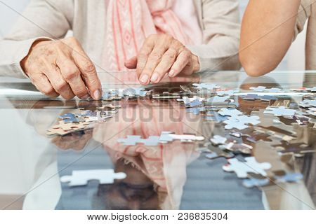 Hands of seniors playing puzzle on the table as a memory training
