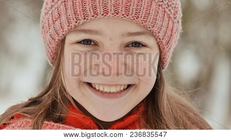Portrait Of A Young Schoolgirl With Freckles In The Woods In Winter. The Girl Touches Her Nose With