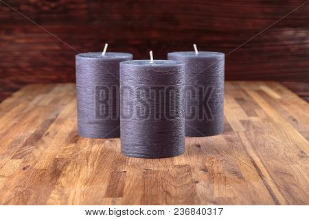 Three Decorative New Candles Are Standing On An Oak Surface On A Dark Background