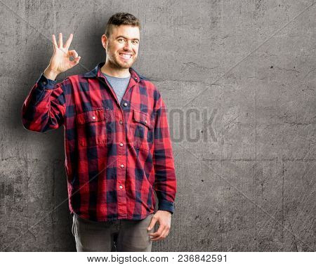 Young handsome man doing ok sign with hand, approve gesture
