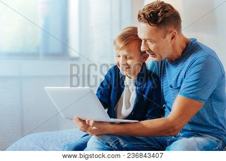 New Device. Cute Positive Happy Boy Smiling And Looking At The Netbook Screen While Sitting Together
