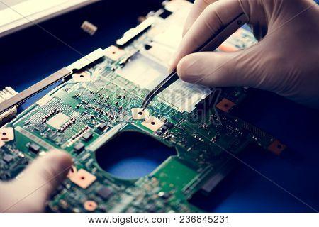 Closeup of hands with computer motherboard and tweezers