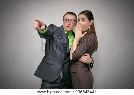 Shocked And Frightened Business Couple Looking Ahead Isolated On Gray Background. Telling The Secret