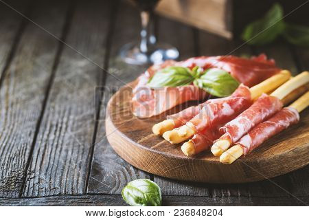 Bread Sticks Grissini With Prosciutto Ham On Cutting Board Over Wooden Background, Close Up