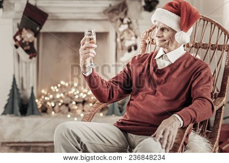 Time To Celebrate. Handsome Pensioner Wrinkling Forehead And Keeping Smile On His Face While Looking