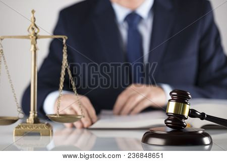 Man In Suit On White Background. Law Business Concept. Judge Gavel, Scale Of Justice And Legal Code.
