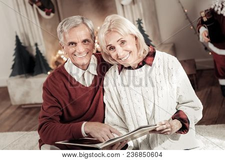 Sweet Memories. Charming Woman Keeping Smile On Her Face And Bowing Head While Holding Interesting B