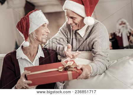 Being Surprised. Delighted Man Expressing Positivity While Talking With His Wife And Wearing Christm