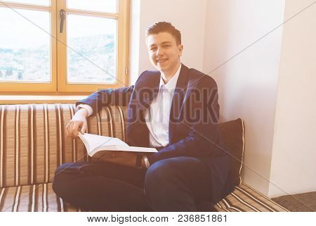 Young Student Learning In Front Of Bright Window