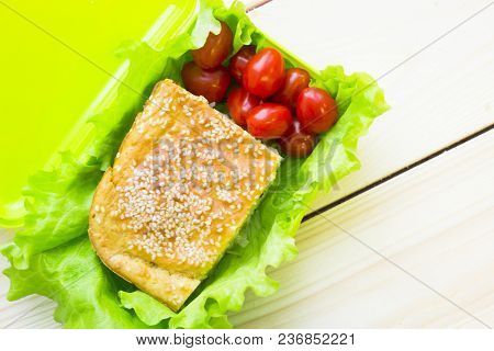 Healthy Lunch Concept. Pie With Seasam, Cherry Tomatoes And Lettuce In A Lunch Box, Light Wooden Bac