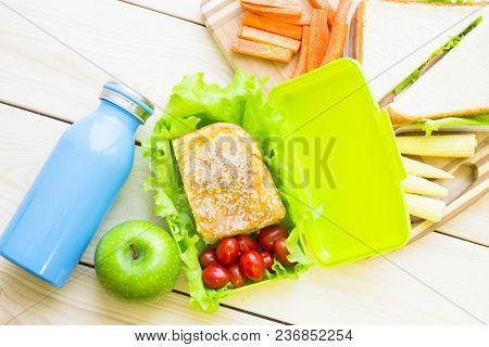 Healthy Lunch Concept. Pie With Seasam, Cherry Tomatoes And Lettuce In A Lunch Box, Apple And A Blue