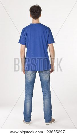 Boy In Blue T-shirt And Jeans Standing Back To Cameraman