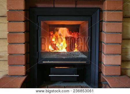 Wood Burning In The Sauna Oven. Brick Backgound.