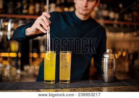 Young Barman In A Blue Shirt Prepares Two Alcoholic Cocktails, Adding Pieces Of Orange To The Ice Us