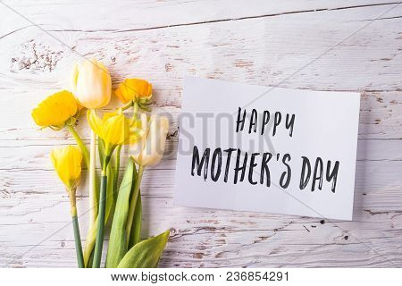 Mothers Day Composition. Happy Mothers Day Note And Bouquet Of Yellow Flowers. Studio Shot On White