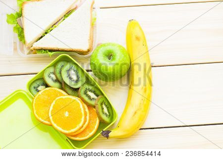 Healthy Lunch Concept. A Green Lunch Box With Sliced Orange And Kiwi, Sandwich In A Box, Apple And B