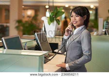 Smiling Vietnamese Hotel Receptionist Talking On Phone