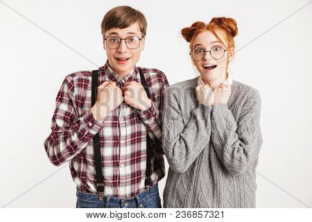 Excited couple of school nerds looking at camera isolated over white background